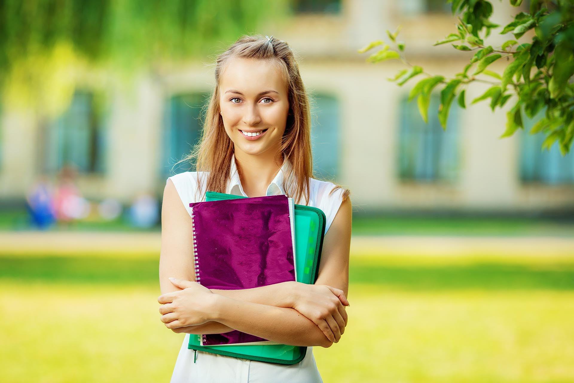 Student woman is standing with the folder and copy-book on the university campus background. Happy smart young woman is going to study outdoors in the park.